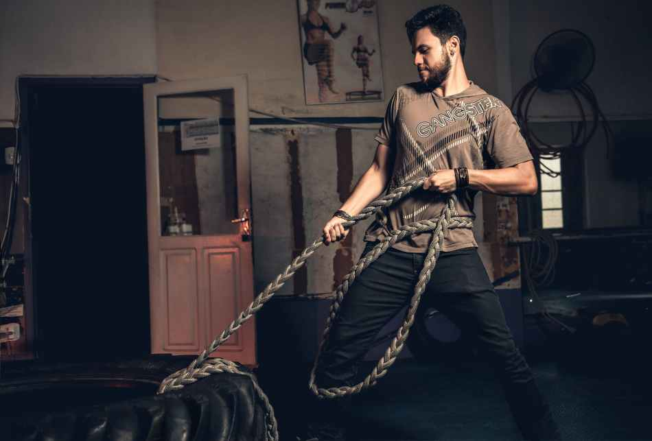 man pulling rope tied on a tire